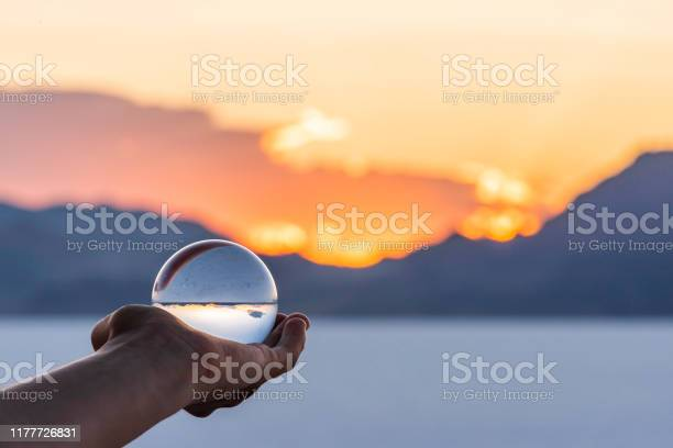 Photo of Bonneville Salt Flats colorful landscape bokeh background with hand holding crystal ball near Salt Lake City, Utah and mountain view and sunset