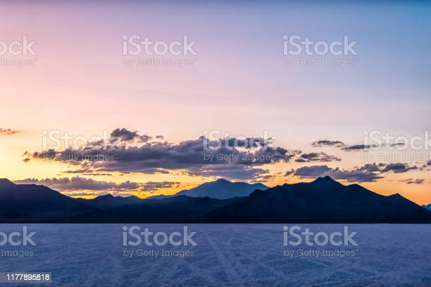 Photo of Bonneville Salt Flats colorful purple dark twilight silhouette mountain panoramic view after sunset near Salt Lake City, Utah with clouds