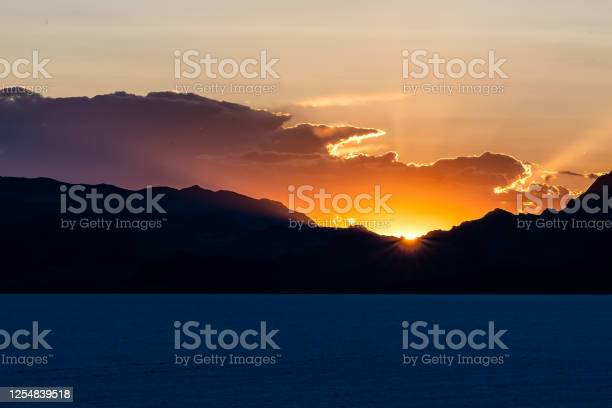 Photo of Bonneville Salt Flats dark blue landscape near Salt Lake City, Utah and silhouette mountain view and sunset sun rays glowing behind clouds