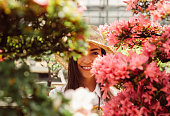 Bonsai greenhouse center. rows with small trees, woman working and taking care of the plants