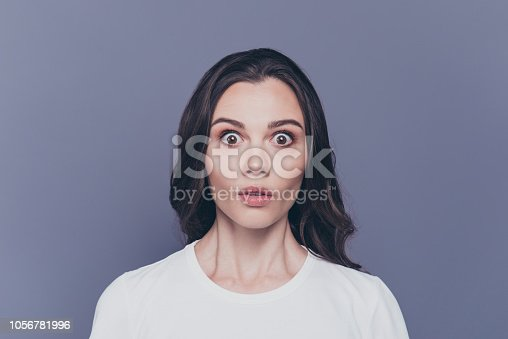 istock Boo! Portrait of attractive pretty charming stylish afraid brunette curly-haired girl in white t-shirt with staring big eyes, isolated over grey background 1056781996