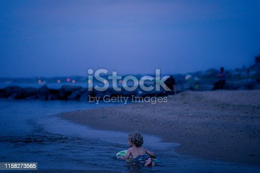 A young boy paddles out on a boogie board at dusk along the shores of Fresh Pond Beach, Amagansett, NY.