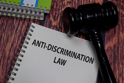 Book about Anti - Discrimation Law isolated on wooden table.