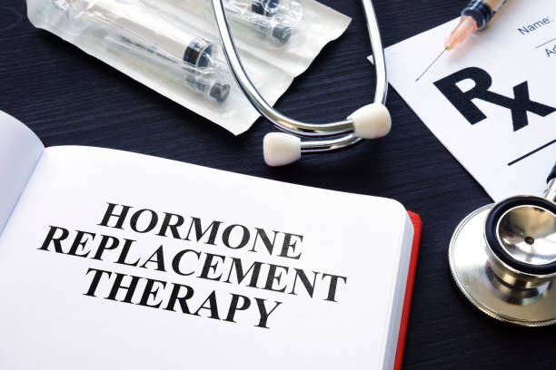 Book about Hormone Replacement Therapy and syringes. stock photo