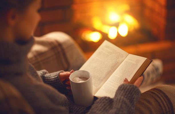 buch und eine tasse kaffee in händen der mädchen am winterabend kamin - behaglich stock-fotos und bilder