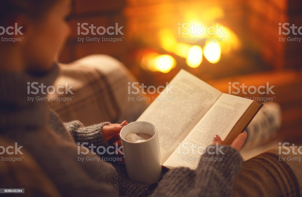 book and cup of coffee in hands of girl on  winter evening near fireplace stock photo