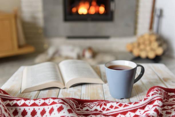 book and cup of tea near fireplace - hygge imagens e fotografias de stock