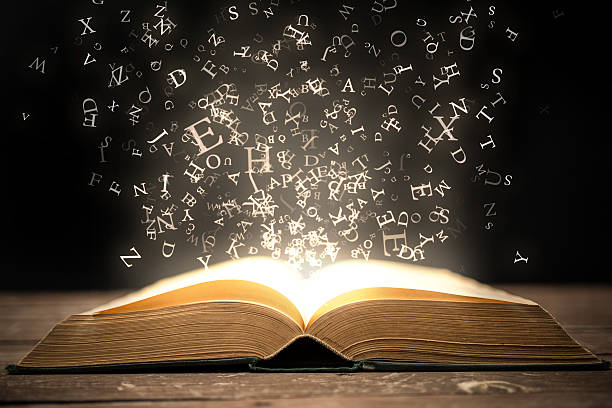 book and glowing letters - literature stock pictures, royalty-free photos & images