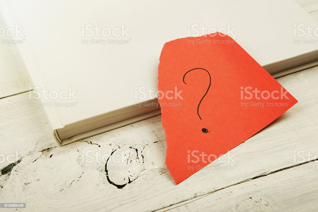 Book and red sheet with a question mark stock photo