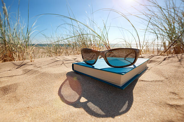 Book and sunglasses on the beach stock photo