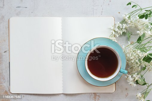 Open blank page book with a copy space and cup of tea on a white wooden table background.