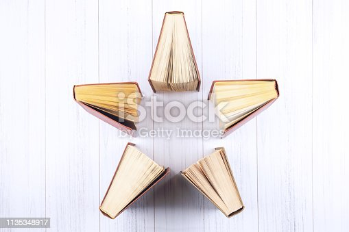 istock Book background. Top view of open hardback books in star shape on wooden table. Education, literature, knowledge, Back to school. Copy space. 1135348917