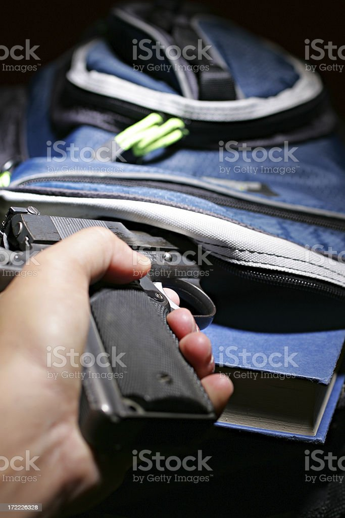 Book bag and a handgun royalty-free stock photo