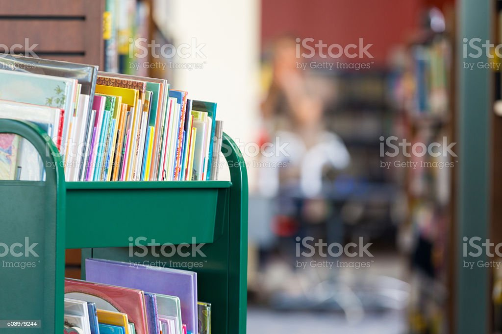 Book cart full of childrens' books in public school library stock photo