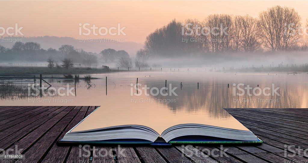 Book concept Landscape of lake in mist with sun glow stock photo