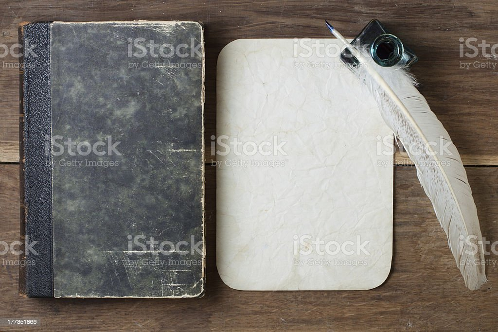 Book cover, quill, inkwell, old grunge paper on wood royalty-free stock photo