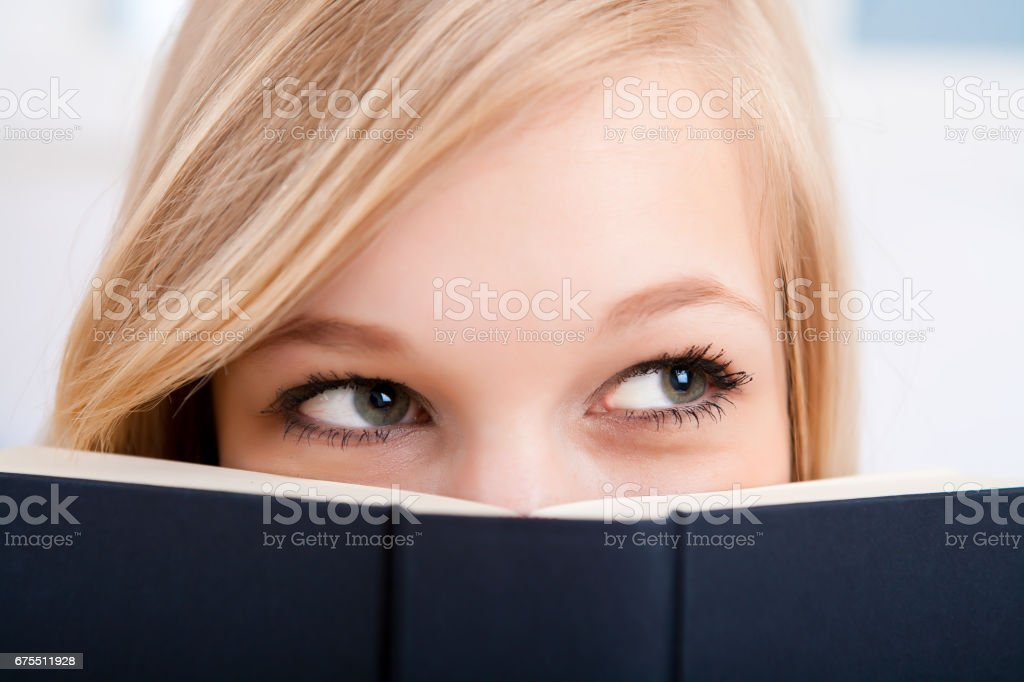 Book covering face stock photo