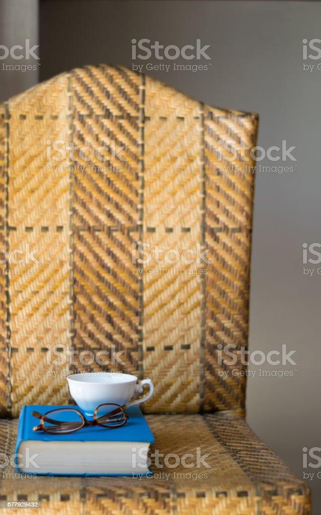 Book, cup and eyeglasses on a chair. royalty-free stock photo