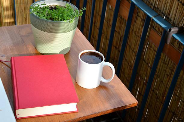Libro, taza de café, planta en maceta mesa en el balcón - foto de stock