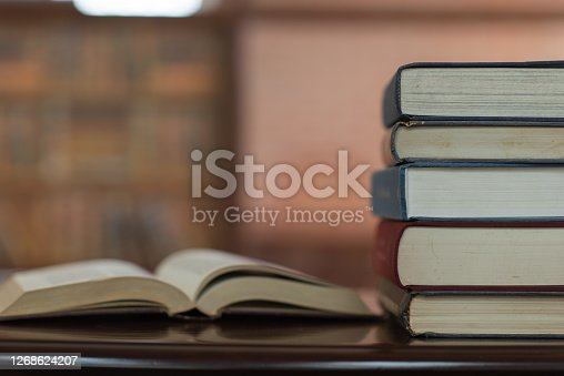 books stack and book open on desk in library. education learning concept.