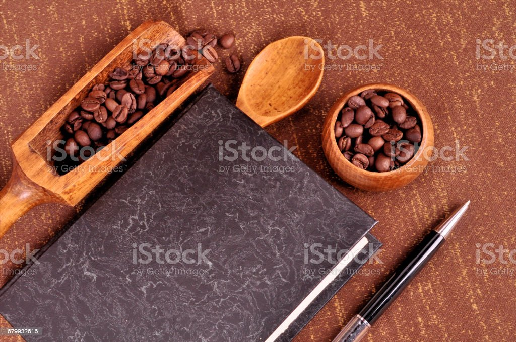 Book for recipes for making coffee. Roasted coffee beans in a wooden bowl stock photo