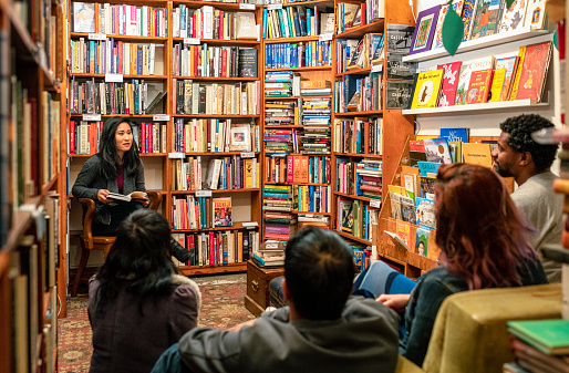 A small group meeting to listen to a book reading in an independent bookshop.