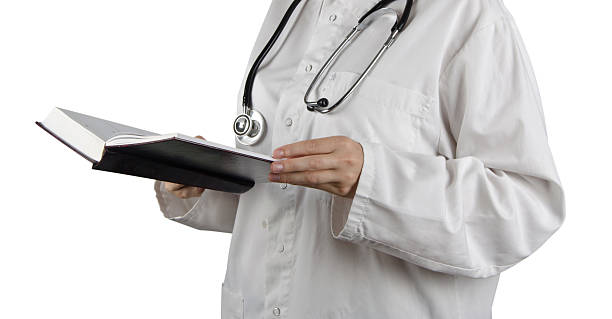 book in doctor's hand - fda stock photos and pictures