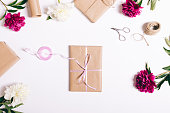 istock Book in wrapping paper with ribbon lies on a white table 691888624