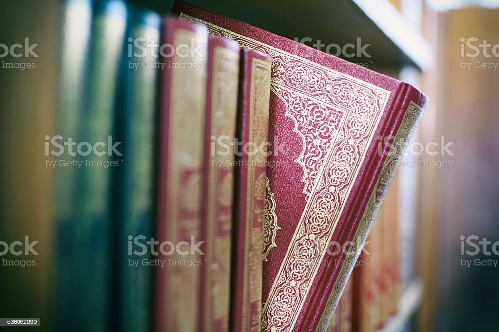 Book is selected from bookshelf with vintage background stock photo
