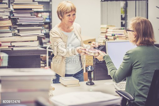 istock Book lending,  librarian and an adult woman with books in library 820912476