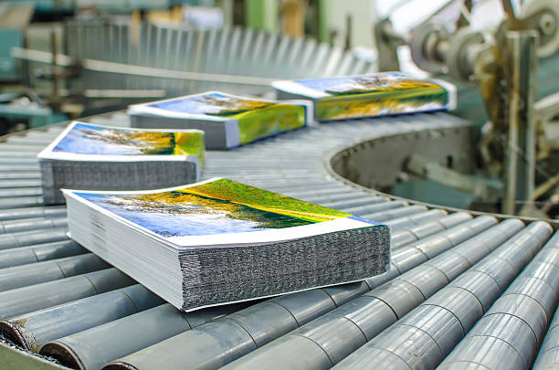 Book, magazine, catalog production line into press plant house. Binding cover and assembling with the spline. printing plant stock pictures, royalty-free photos & images