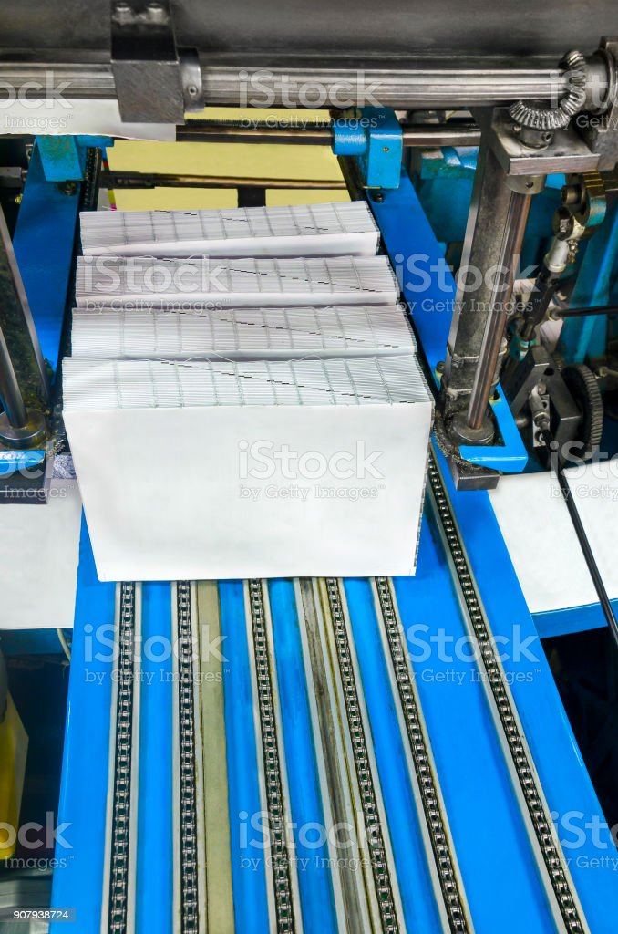 Book, magazine, production line into press plant house. Automatic assembly line stock photo