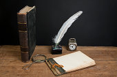 istock Book, magnifying glass, old notepad, quill, inkwell, clock on table 177030412