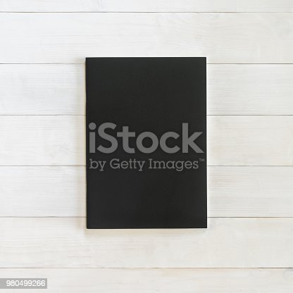 887572514istockphoto Book mockup blank black leather A4-size cover page template flat lay on white wood table from top view 980499266
