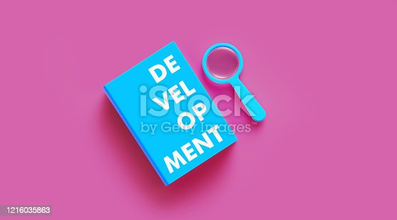 istock Book of Development Next to Blue Magnifier Sitting Over Pink Background 1216035863