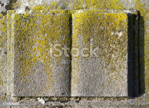 An open book shape is carved into a very old and moss covered headstone. Wonderful grunge background.