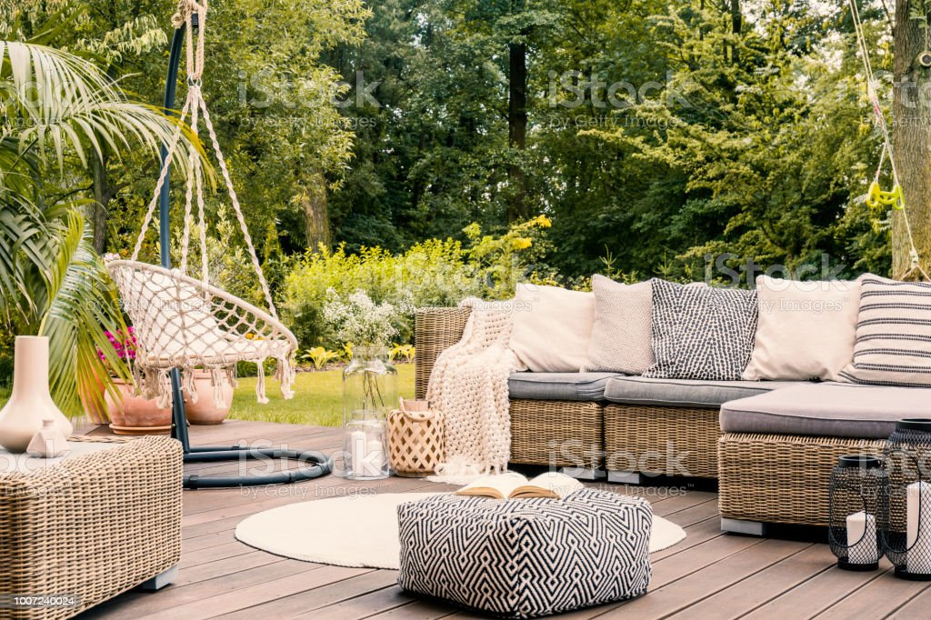 Book on a black and white pouf in the middle of a bright terrace with a rattan corner sofa, hanging chair and round rug. Real photo stock photo