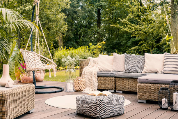 Book on a black and white pouf in the middle of a bright terrace with a rattan corner sofa, hanging chair and round rug. Real photo Book on a black and white pouf in the middle of a bright terrace with a rattan corner sofa, hanging chair and round rug. Real photo lawn stock pictures, royalty-free photos & images