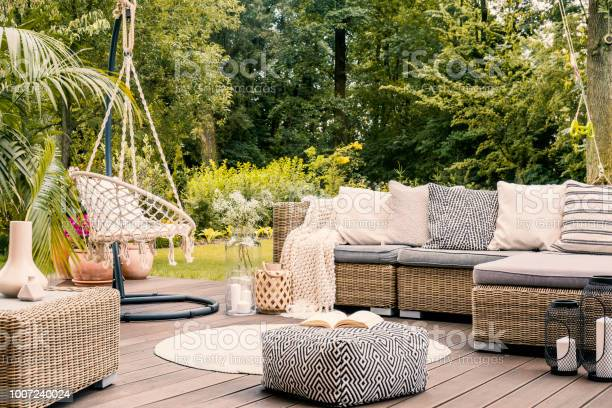 Photo of Book on a black and white pouf in the middle of a bright terrace with a rattan corner sofa, hanging chair and round rug. Real photo