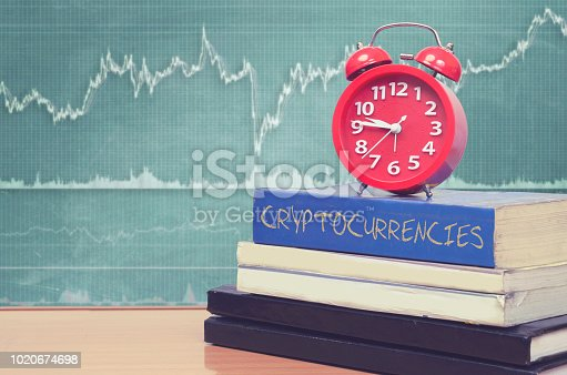 Book of cryptocurrency and trading chart in background in blackboard