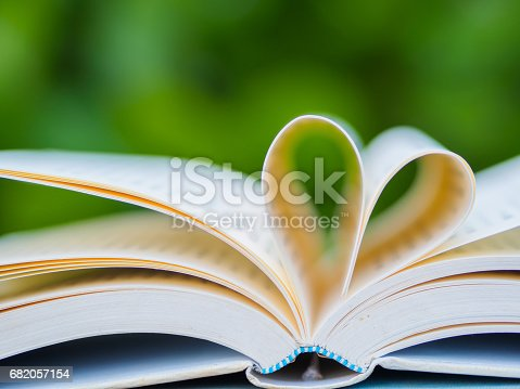 503130452istockphoto book on table in garden with top one opened and pages forming heart shape 682057154