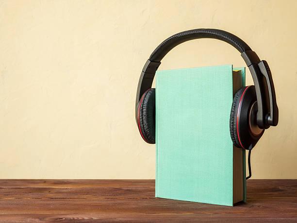 libro sobre la mesa con auriculares - auriculares equipo de música fotografías e imágenes de stock