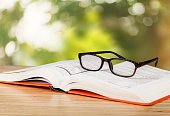Close-up view of open book and eyeglasses