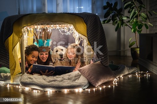 Happy nanny reading a book while relaxing small girls and a dog in a tent in the living room.