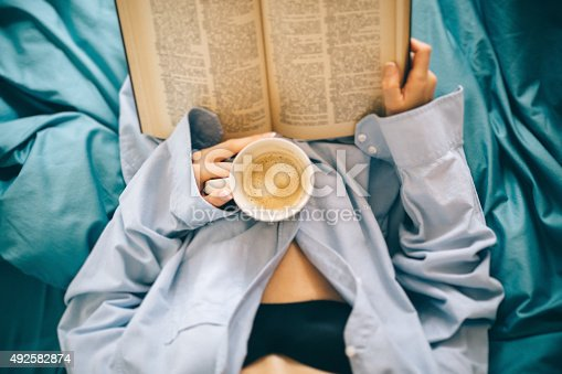 Girl in bed with coffee reading a book