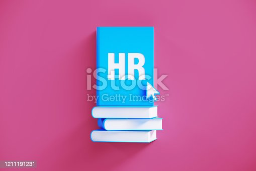 HR book sitting above a blue book stack over pink background. HR written on the books and there is an arrow cursor over the books. HR and recruitment concept.