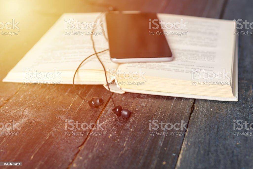 livro, smartphone, fones de ouvido em um fundo de madeira - foto de acervo