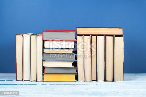 istock Book stack, hardback colorful books on wooden table and blue background. Back to school. Copy space for text. Education concept 689449208