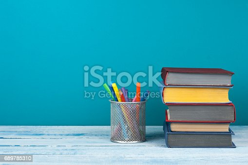 istock Book stacking. Open book, hardback books on wooden table and blue background. Back to school. Copy space for text 689785310