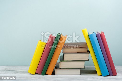 istock Book stacking. Open book, hardback books on wooden table and blue background. Back to school. Copy space for text 690360282